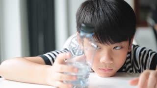 Happy asian cute boy drinks water from a bottle .
