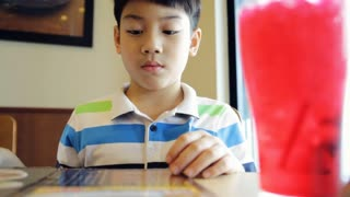 Happy Asian cute boy reading menu book and point .