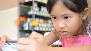 Happy Asian cute child playing and touching with smart phone