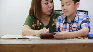 Happy asian family boy and parent looking cellphone and drawing together