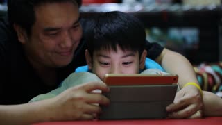 Happy asian family Father and son looking on tablet screen, in the bedroom