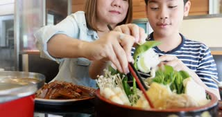 Happy asian family mother and son enjoy eating