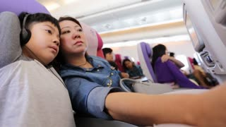 happy asian family playing and watching monitor on air plane