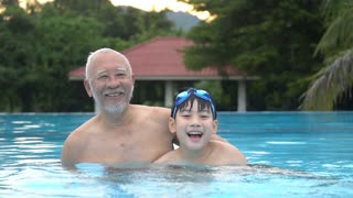 Happy asian family playing in pool, Asian grandchildren and grand parents swimming in pool.