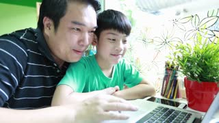 Happy Asian father and son are browsing the internet on laptop computer .