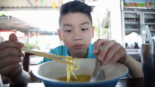 Happy asian kid eating noodles