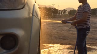 Happy asian kid washing car with water spray .Slow motion shoot with sunset and flare ,120 Fps By Sony A6300