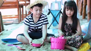 Happy asian kids playing sand on beach