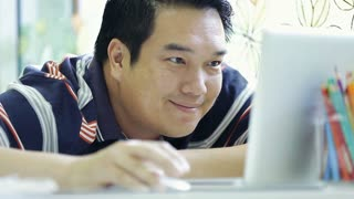 Happy Asian man using his laptop and smile
