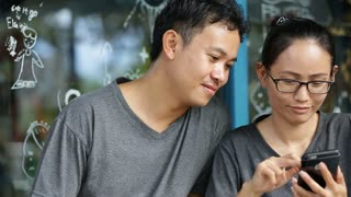 Happy asian man with girl friend using cell phone together .
