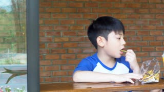 Happy asian mom with her son eating snack and playing together make fun
