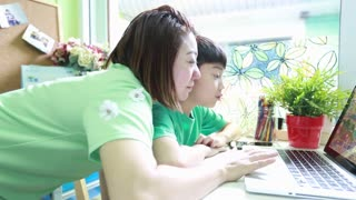 Happy Asian Mother and son are browsing the internet on laptop computer .