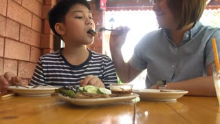 Happy Asian mother with her son eating lunch at home,happy asian family enjoy with meal