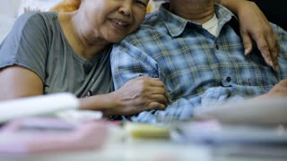Happy asian senior man and woman hugging and smiling in front of camera.