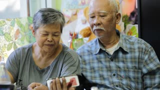 Happy asian senior man and woman using smart phone together,with smile face .