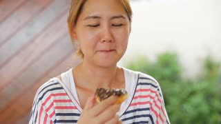 Happy asian woman enjoy eating donut sweet food