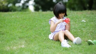Little asian boy and girl blowing soap bubble in the park