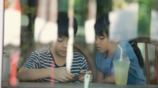 Little Asian boy and girl playing cell phone together in restaurant .