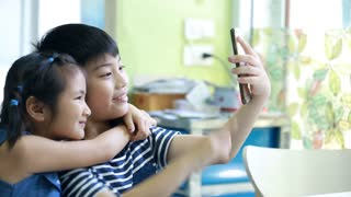 Little asian boy and girl take a photo with cell phone