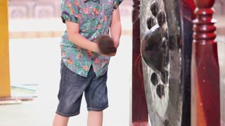 Little asian boy bangs on a large Antique Thai Gong( Bell)/These Gongs were traditionally found outside Buddhist Temples in Thailand.