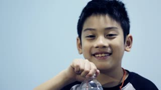 little asian boy drinks water from a bottle