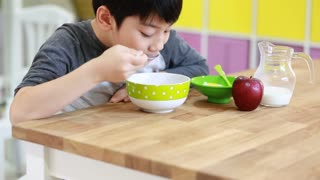 Little asian Boy eating cereal with milk with smile face
