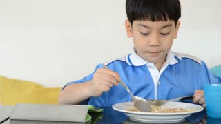 Little asian boy eating fried rice and playing tablet computer .