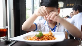 little Asian boy eating spaghetti at restaurant with smile face