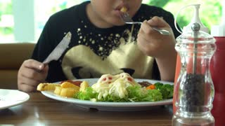 little Asian boy eating steak with vegetable Salad at restaurant with smile face