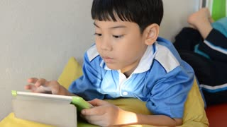Little asian boy smiles and playing tablet computer acting on his face