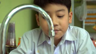 Little asian boy washing hand and looking at camera with smiling face