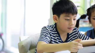Little asian boy with tablet computer and little girl playing together