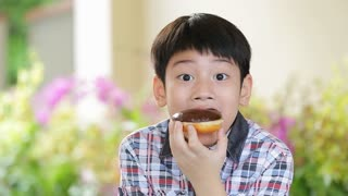Little asian child eating donut sweet food