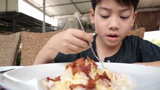 Little asian child eating pasta at restaurant .
