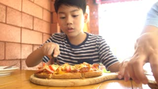 Little asian child eating pizza at restaurant .happy asian boy enjoy at your meal.