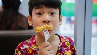 Little Asian child enjoys eating fried chicken .
