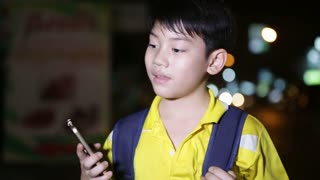 Little asian child playing with smart phone on night lights background
