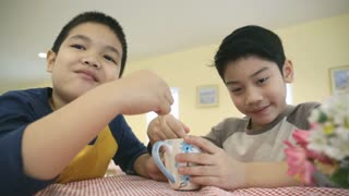 Little asian children enjoy eating ice cream together