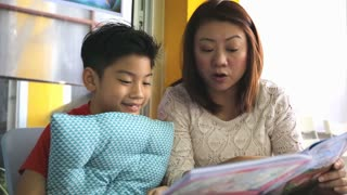 Little Asian cute child with mother reading book in library