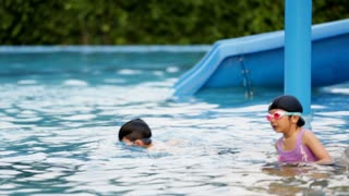 Little Asian cute girl practices swimming with her brother. Asian family.