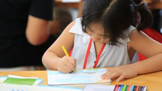 Little Asian girl drawing a picture on the table