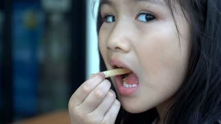 Little asian girl eating french fries and looking camera. Slow motion 120 Fps By Sony A6300