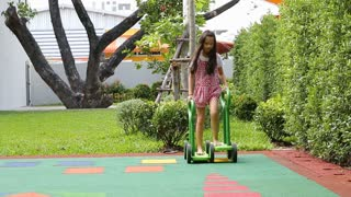 Little asian girl riding fast a push Carting / cart at the playground / park