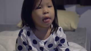 Little asian girl watching television on the bed
