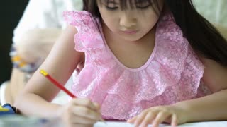 Little Asian girl with mother doing your homework on the table