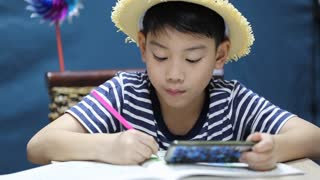 little asian happy boy looking on screen of cell phone and painting, with smile face