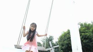 Little Asian happy child enjoy swing in the park
