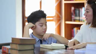 Reading with teacher - an elementary school boy reads aloud to her teacher