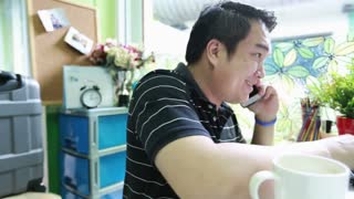 Shot of asian businessman using a laptop while talking on mobile
