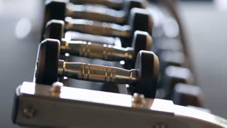 Sports dumbbells rubber in modern sports club. Weight Training Equipment. Camera in motion